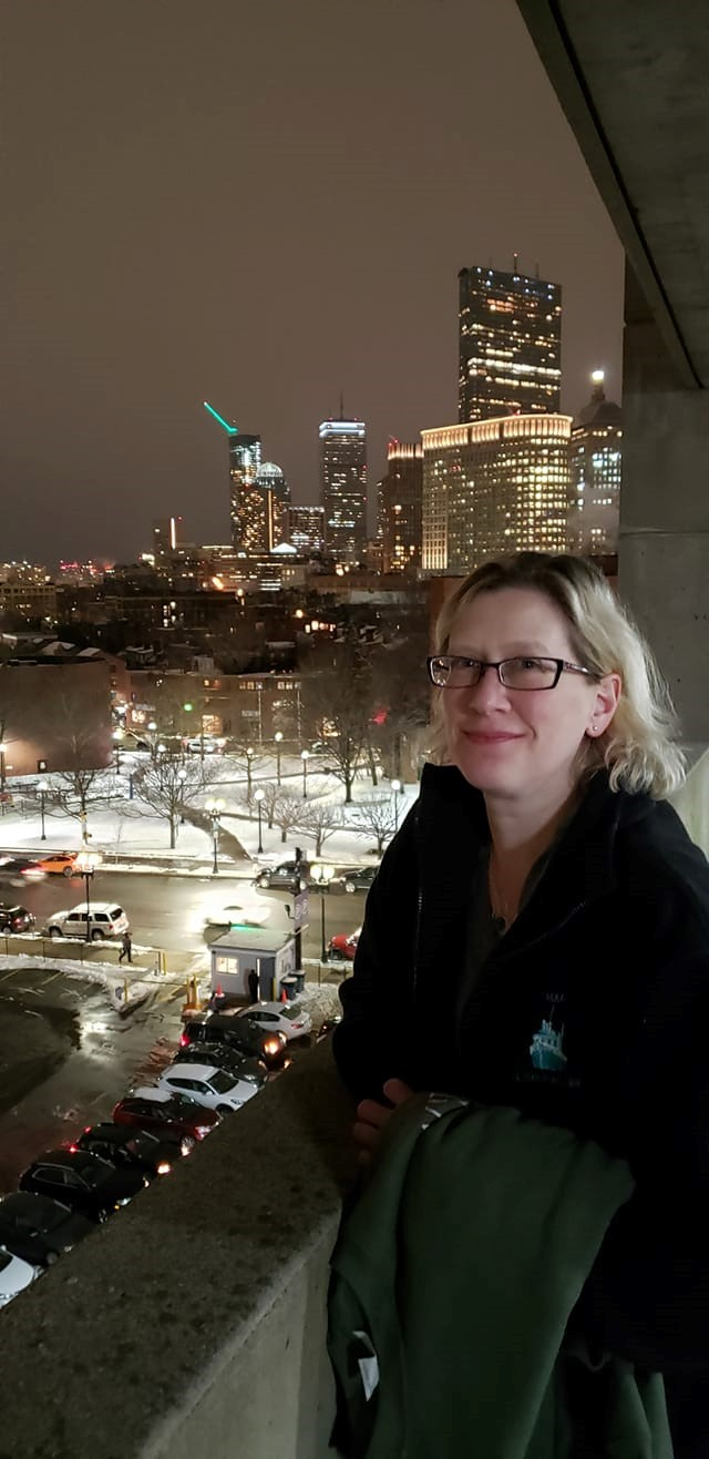 Abby Kingsbury in Boston with the nighttime city skyline behind her